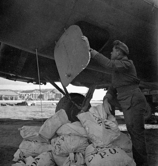 An overseas aircrew member removes mail from Canada out of the belly of a Rockcliffe B17