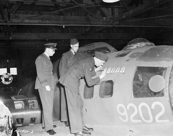 "RCAF aircrew paint a mailbag ""kill"" on the side of the B17 after another successful mail mission from Rockcliffe to the war in Europe/North Africa"