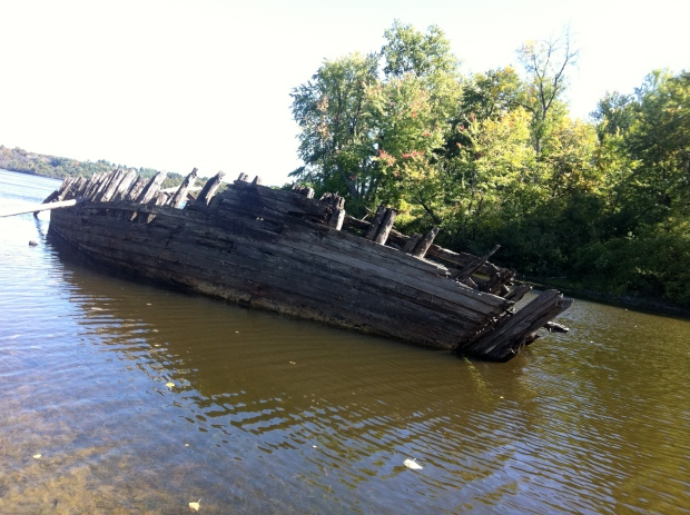 The wooden hull listed to one side in about 8 feet of water.