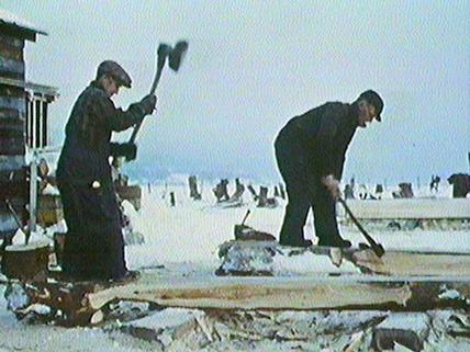 "A still from the NFB film ""jean Richard"" showing workers using adzes to shape the timbers for the ship's hull."