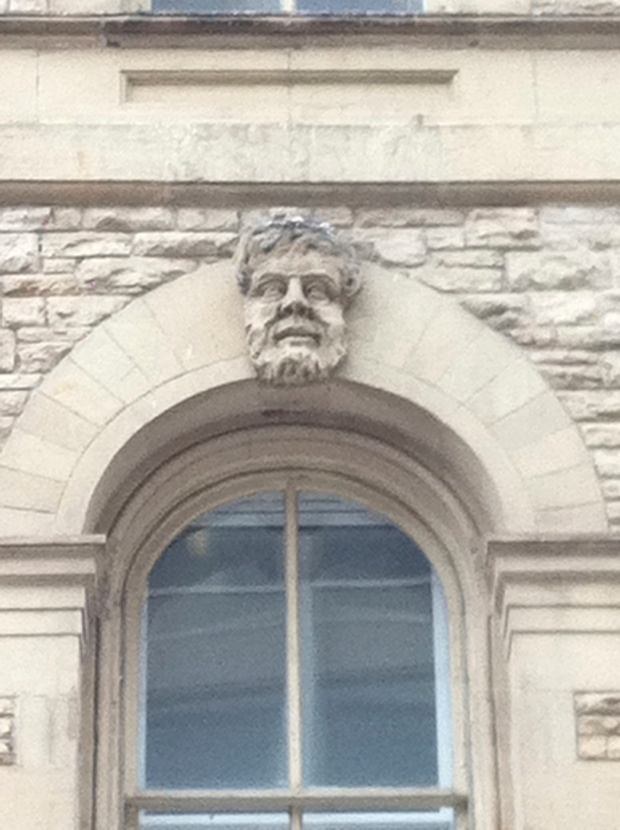 The only one of the eleven carved heads on the building that has a grin.