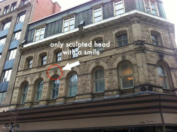 At 93 Sparks St. in Ottawa 11 scowling heads adorn a historic building. However, one of the heads is oddly smiling.